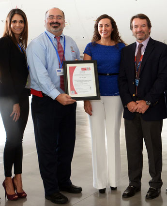 Enrique Guzmán, Environmental Senior Manager at LAN, proudly presents the ISO certificate. He is flanked by two female LAN executives and LAN Cargo's CEO Cristian Ureta  -  courtesy LAN Cargo
