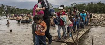 Migrantes venezolanos cruzan en 2019 el río Táchira, en oeste de su país para ingresar en Colombia. Foto: Vincent Tremeau/Acnur