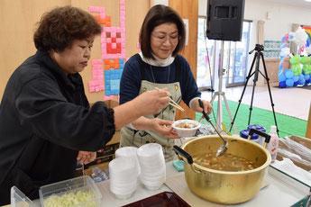 会場入り口ですいとんを振る舞う馬上さん(左)と平田さん(右)。具だくさんの汁とすいとんの美味しさに、おかわりをする人の姿も多く見られた