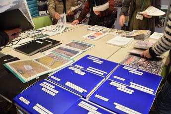 会議開催に向けて、各町村から集まった資料の展示と、それを閲覧する人たち