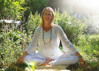 Ein Mensch umgeben von strahlend weißen geometrischen Formen und leuchtender Aura sitzt im Lotussitz vor einem violetten Universum.