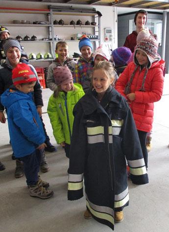 Anna probiert den Mantel des Feuerwehrmannes an.