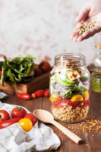 Ein Salat im Glas mit Bulgur, Tomate, Paprika, Avocado und Tofu