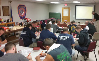 Firefighters taking an exam at the end of the extrication tool training