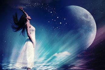 femme , les pieds dans l'eau sous la lumiere de la lune