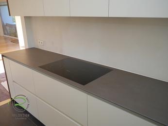 Moderne Küche in weiß mit flächenbündig eingelassene Ceran-Kochfeld in weiß und Nussbaumdekor von Schreinerei Holzdesign Ralf Rapp in Geisingen