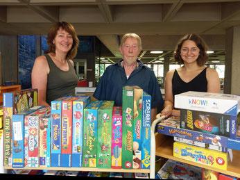 Ein Teil der neuen Spiele, Doris Hammerbacher und Franziska Meyer aus der Stadtbibliothek und Jürgen Höhn vom Spieleclub Neumarkt. Foto: Hauke Höpcke