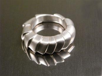 Silberner Ring mit geschachtelten Flächen gestaltet.