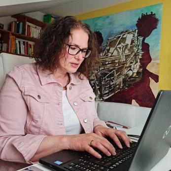 """Miriam Pietrangeli sitz am Schreibtisch und schreibt am Laptop. Im Hintergrund sieht man ihr Bild """"Sogno"""""""