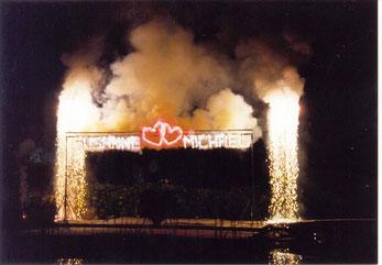 Lichtbild mit Namenszug - eingefasst von einem pyrotechnischen Wasserfall
