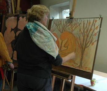 een vrouw tekent met krijt op een groot formaat papier. Op de tekening stat een vrouw op haar knieën met gebogen hoofd, helemaal oranje  en ook de omgeving is warm van kleur.