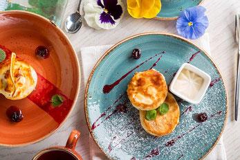 朝食の皿。チーズケーキ。コーヒー。ハイビスカスの花びら。