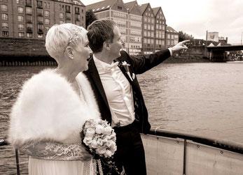Hochzeit auf der Nedeva, Portraitaufnahme auf dem Schiff Vorderdeck, Blick in Richtung Staphanibrücke in Bremen, Bräutigam zeigt mit Hand Richtung Beck´s Bremen