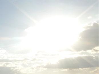Weiße Wolke am Himmel, die durch die dahinter stehende Sonne sehr hell strahlt und vier Strahlen in vier Richtungen abgibt