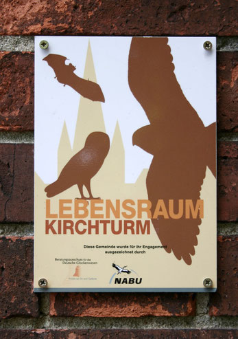 """Plakette """"Lebensraum Kirchturm"""" an einer Kirchenmauer"""
