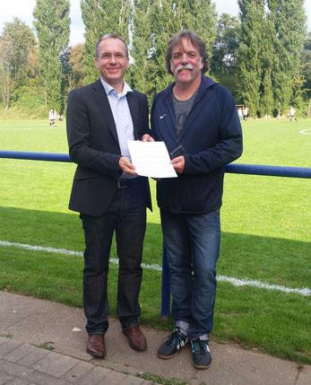 André Dora und Martin Kindermann halten den Pachtvertrag in ihren Händen, der heute bei de Heimspiel unserer ersten Mannschaft übergeben wurde.