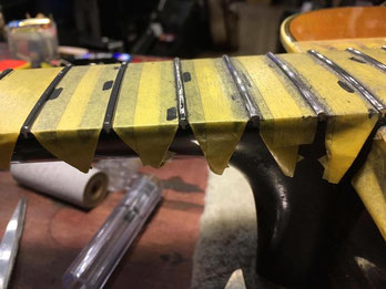 ギターネックに取り付けられた、やすりがけする前のステンレスフレット