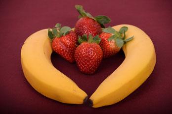 Deux bananes forment un cœur avec, à l'intérieur, quatre fraises bien mûres
