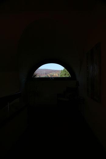 Immobilienfoto: Blick durch ein halbrundes Fenster, nur die Landschaft draußen sichtbar