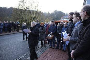 Dies- und jenseits der Bundesstraße in Bad Rehburg stehen die Menschen während Fritz Erich Anhelm die Stolperstein-Verlegung in Bad Rehburg moderiert.