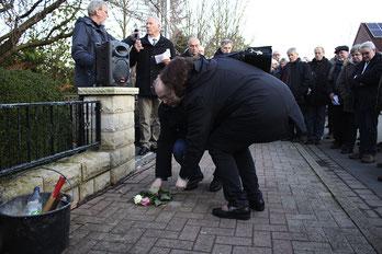 Ingo Harmening legt mit einer Angehörigen der Familie Busack Rosen am Stein für Jeanette Busack nieder.