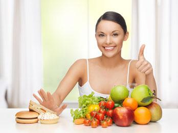 Eine Frau, die Fastfood und gesundes Obst und Gemüse zur Auswahl hat und sich für die gesunde Ernährung entscheidet.
