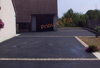 Aménagement d'une cour en enrobé noir avec des lignes de pavés en décoration