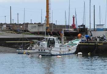 神奈川県・真鶴漁港の赤い灯台と漁船