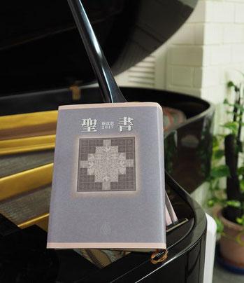 教会堂にあるグランドピアノと聖書の写真