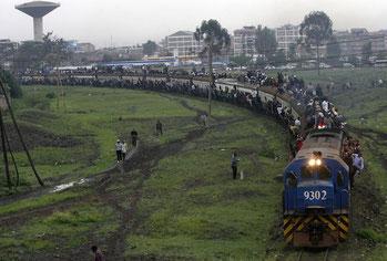 I passeggeri cavalcano le carrozze sovraccariche di un treno di pendolari nella capitale del Kenya, Nairobi