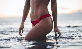 Schlanke Frau in rotem Bikini mit Bauchnabelpiercing steigt aus Wasser