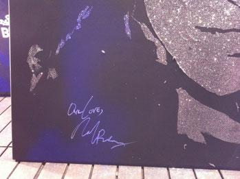 Signature de Michelle Rodriguez sur la toile de son portrait glitter painting