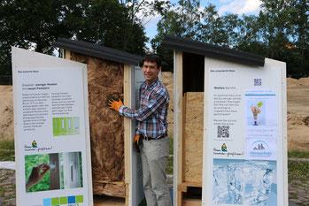Holzhäuschen mit und ohne Dämmung. Klimaschutzmanager in der Mitte.