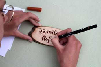 Familienname wird per Handlettering auf eine ovale Holzscheibe aus Eschenholz geschrieben.