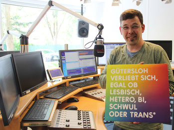 """Radio Gütersloh-Moderator Mario Unger mit dem Plakat von """"Gütersloh verliebt sich"""""""