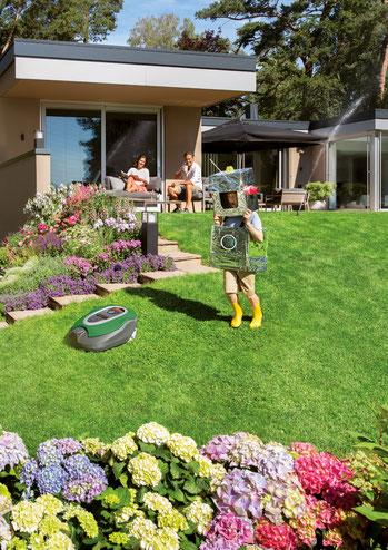 Familie im Garten mit einem Rasenroboter