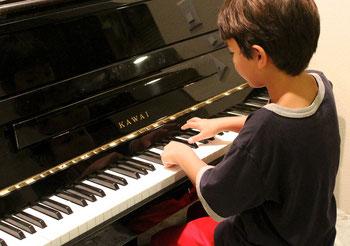 Spielerischer Klavierunterricht für Kinder   Junge spielt Klavier