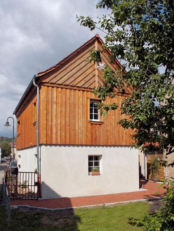 mit Holz verkleidetes Haus, Giebelansicht, sonnenbeschienen