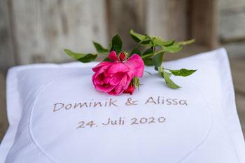 Wunderbare Erinnerung an einen unvergesslichen Tag. Hohzeitskissen mit von Hand gestickten Namen und Hochzeitsdatum als personalisiertes Geschenk