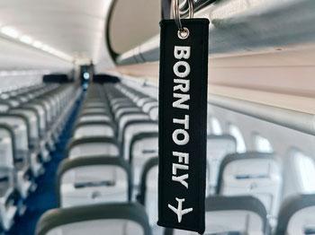 Born to Fly. Gepäckanhänger in Flugzeugkabine.