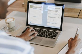 Bild zeigt einen Menschen der Aufgaben auf einem Laptop löst.