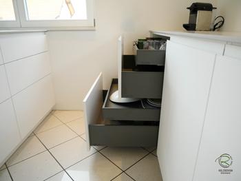 grifflose, weiße Design Küche mit oriongrauen Schubladen von Blum Legrabox mit Halbkochinsel 12 mm Keramik Arbeitsplatte