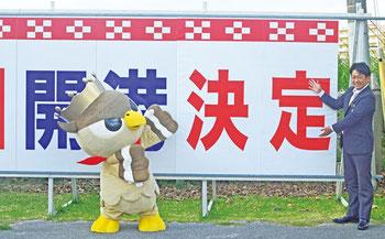 中山市長とぱいーぐるが覆っていた紙を取り、「決定」の文字を浮かび上がらせた=石垣空港