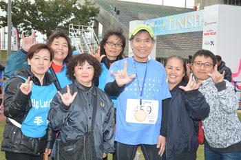 神奈川県からフルマラソンに出場した榎本さん(中央)を支えた手話通訳ボランティアのスタッフら=22日午後、石垣市中央運動公園陸上競技場