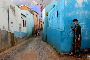 Mia on the corner of a colorful street in the Vila