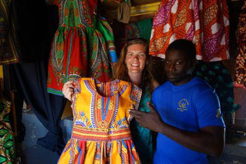 Trying on a colorful dress at the Sucupira market in Praia, Santiago