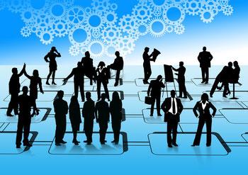 verschiedene Menschen stehen in unterschiedlichen Gruppen zusammen auf einem blau gekachelten Boden. Oben Hälfte des Bildes zeugt diverse Zahnräder, die ineinander greifen.