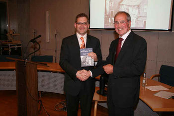 Josef Bechler übergibt das Buch am Bürgermeister Himmel