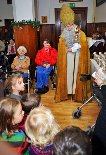Der Nikolaus mit seiner goldenen Mitra und seinem goldenen Bischofsstab ist umgeben von älteren Menschen im Rollstuhl und von jungen Kindern, die erwartungsvoll auf den Schokonikolaus schauen.