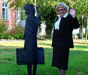 Zweimal Paula: neben der stählernen Skulptur von sich selbst beim Abschied vor 75 Jahren steht Paula Calder und winkt.